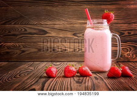 A large glass jar with strawberry smoothies stands on a large brown wooden table. A long, thin straw and one strawberry on top of the jar. A few strawberries are near a full can of strawberry fresh.
