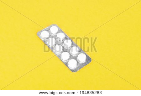 A single packaging of bright white pills. Tablets in blisters. Packs of painkillers, antibiotics on a light yellow background. Medicinal prescripted drugs.