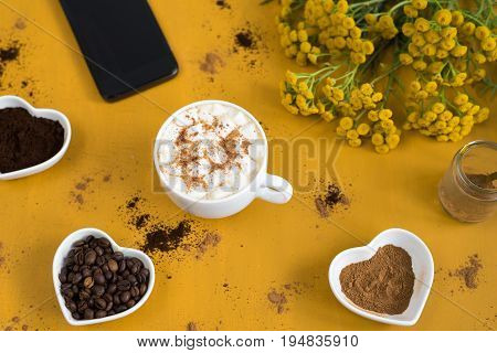 Time for coffee and smartphone. Cup of coffee with marsh-mallows, a smartphone, three bowls filled with beans, powder and cinnamon and yellow wildflowers on a bright yellow background.