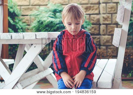 Little boy feeling sad outdoor in terrace.