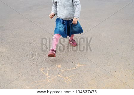 Four-year-old girl with a piece of chalk dancing on asphalt over her drawing. Her face is not seen. She is wearing a demin dress.