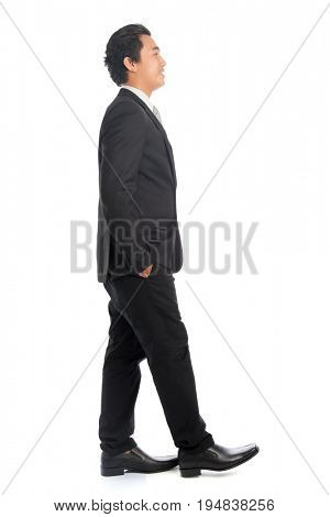 Full body side view of attractive young Southeast Asian businessman walking, isolated on white background.