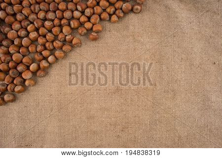 Natural unbroken hazelnuts on a jute bag background. Top view.