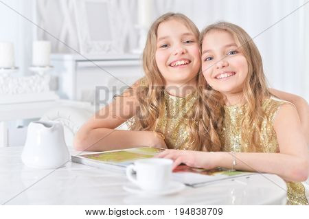 Portrait of cute twin sisters sitting at kitchen table with modern magazine