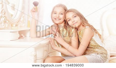 Portrait of a cute twin sisters sitting