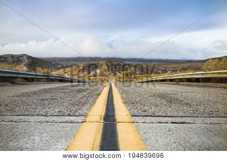 Road in California with mountains in the background and yellow road marking