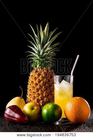 Still Life With Tropical Fruits And  Glass Of Juice On A Black Reflective Background With Drops Of W
