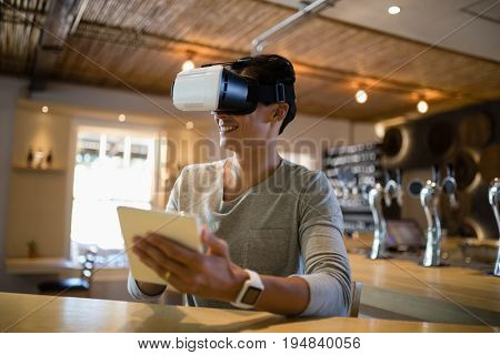 Smiling man using virtual reality headset and digital tablet in restaurant
