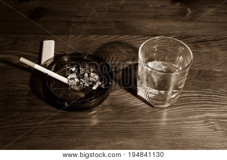 Smoking cigarette in the ashtray and glass with alcohol drink on the bar table. Alcohol and cigarette addiction.