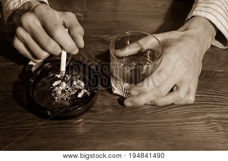 Hands of smoker man with alcohol drink in the bar. Alcohol and cigarette addict.