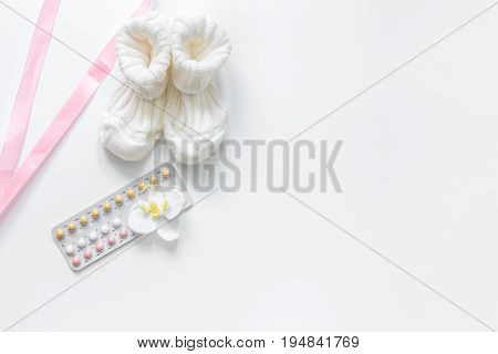 Pregnancy planning. Contraceptive pills and booties on white background top view.