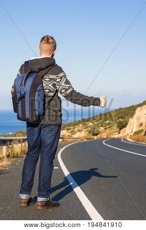 Young caucasian man seen from behind carrying a backpack hitchhiking in a minor road, with his thumb up.