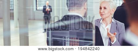 Mature businesswoman with investor talking in industrial interior panorama