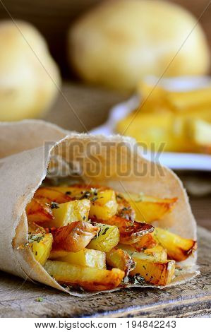 Crispy fried potatoes with spices. Delicious fried potatoes in paper and on a wooden table. Simple potato recipe. Vertical photo