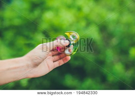 Close Up Of A Man's Hand Who Is Holding A Fidget Spinner In A Park