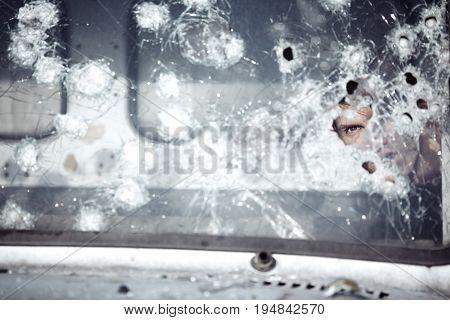 Man behind broken glass of the car