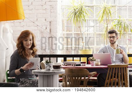 Two hipsters working in modern cafe with colorful furniture