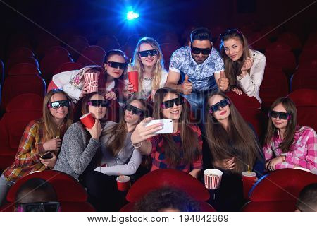 Group of cheerful young friends taking a selfie with a smart phone together while enjoying a 3D movie at the cinema technology gadget social device happiness friendship entertainment leisure concept.
