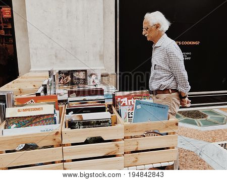 Milan Italy - June 11 2017: elderly man stands in counter with books on art and painting