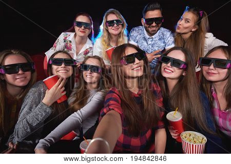 Diverse group of friends wearing 3D glasses making a selfie together while at the movie theatre friendship people togetherness celebration party weekend meeting holidays entertaining unity diversity.