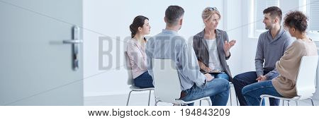 People discussing problems with psychologist during depression group therapy