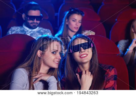 Attractive young women watching a movie together. Female friends chatting while enjoying a film premiere at the movie theatre entertaining technology 3D viewer spectators audience activity friendship.