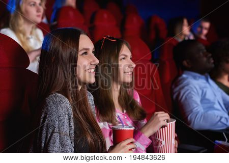 Attractive young cheerful female friends enjoying watching a movie at the cinema together enjoyment recreation entertainment happiness positivity emotions concept.