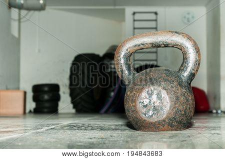 Old rusty kettle bell on the gym floor. Kettle bell training.