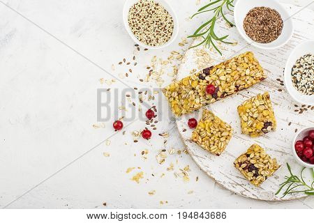 Cereal bars with red berries, honey for a healthy snack on a light background with flax seeds, sesame. Top View.