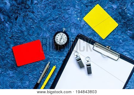 Set to judge competition. Yellow and red cards, stopwatch, whistle, pad, pen on blue table background top view.