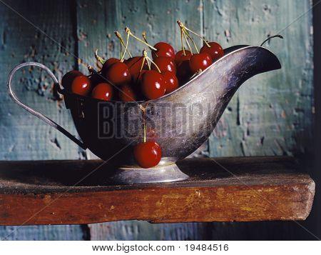 cherries in a silver gravy boat on a wooden shelf