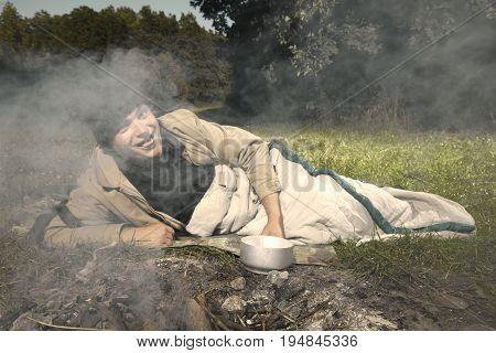 Vagabond young man sleeping in park near illegal fireplace