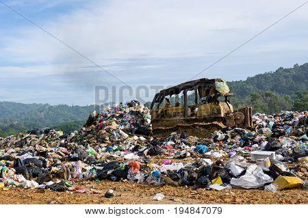 KOTA KINABALU MALAYSIA - 09 JULY 2017: Bulldozer truck flattening household garbage on a landfill waste site in Sabah.