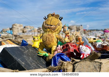 Kota Kinabalu, Malaysia - 09 July, 2017: An Abandoned Dirty Garfield And Other Toys At The Landfill