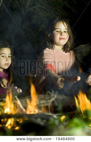 two girls having fun at a bonfire