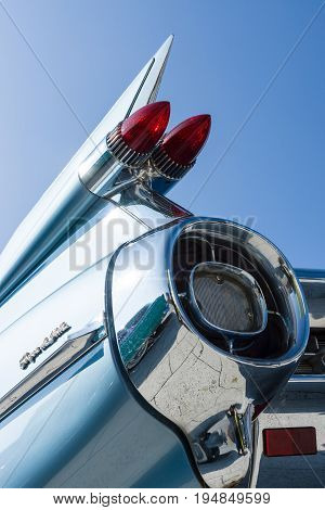 STUTTGART GERMANY - MARCH 18 2016: Detail of the rear wing and brake lights of the car Cadillac Coupe de Ville on the background of blue sky. Europe's greatest classic car exhibition