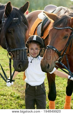 Pretty little girl jockey communicating with her horses in professional outfit
