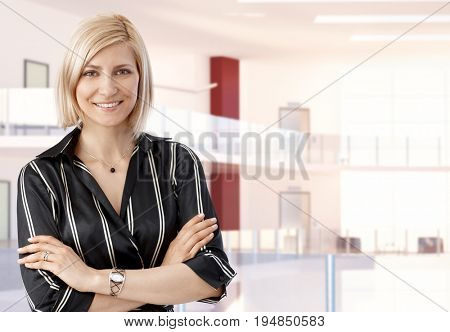 Elegant casual blonde Mid adult businesswoman at busines office center, arms crossed, smiling, looking at camera, copyspace.