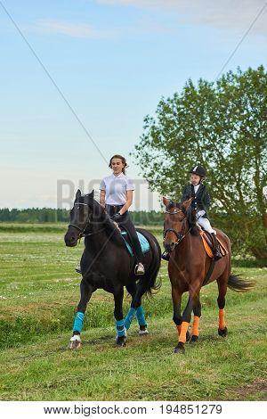 Pretty little girl jockey and her coach ridding a horse