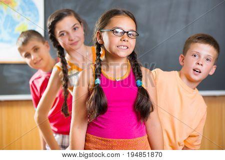 Four Schoolchildren Standing In Classroom Against Blackboard