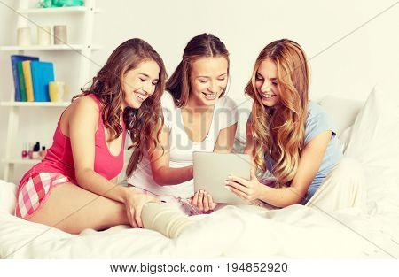 friendship, people, pajama party and technology concept - happy friends or teenage girls with tablet pc computer at home