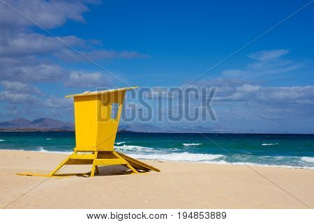 Yellow lifeguard tower. One life guard together with red flag on beach. Point of safe, surviving. Coastal view.