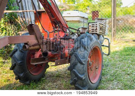 Gasoline motor cultivator in village yard ready to agriculture works