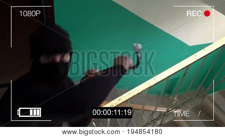 the masked robber breaks removing the surveillance camera mount.
