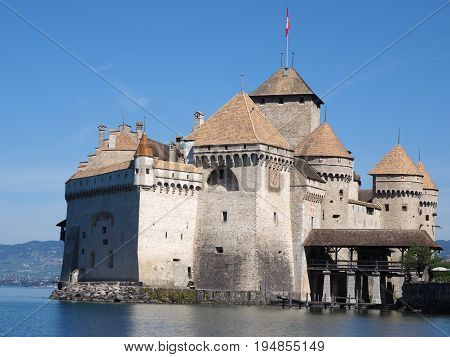 Chateau de Chillon, SWITZERLAND / EUROPE on JULY 2017: Medieval swiss castle on Lake Geneva (Lac Leman) in Canton of Vaud with beautiful alpine landscape and clear blue sky in warm sunny summer day.