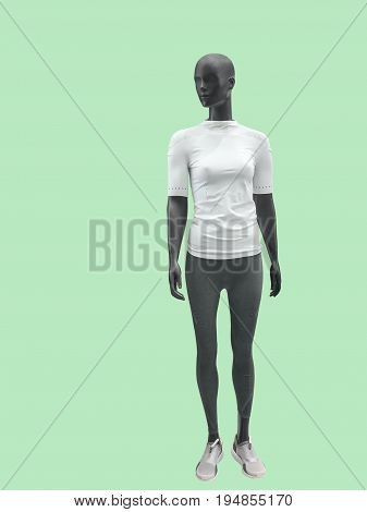 Full-length female mannequin dressed in sportswear isolated on green background. No brand names or copyright objects.