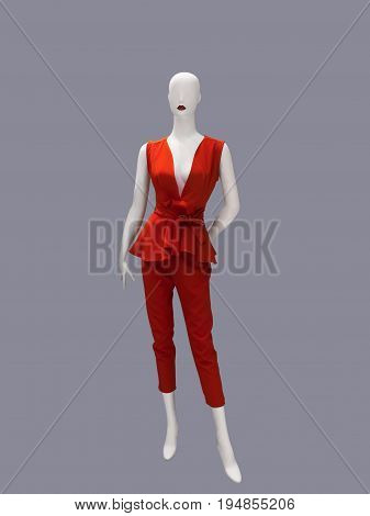 Full-length female mannequin dressed in fashionable red suit. No brand names or copyright objects.