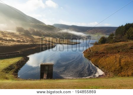 Spillway at the Dove stones reservoir with slightly mist and blue sky Oldham Saddleworth UK