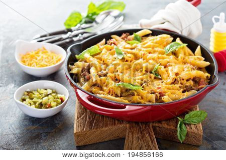 Cheesy pasta bake in a pan with ground beef and herbs