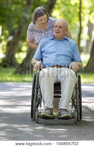 Senior woman pushing husband in wheelchair outside in summer park.